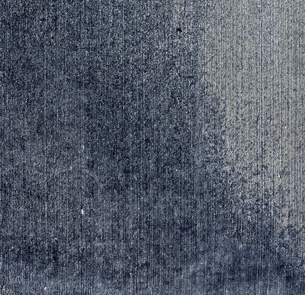 Fine art abstract photograph of a concrete sidewalk with blue jeans texture.