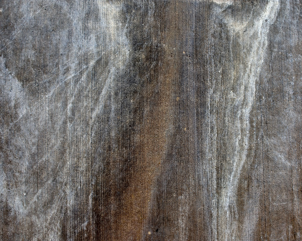 Fine art abstract image of water stains in concrete sidewalk.